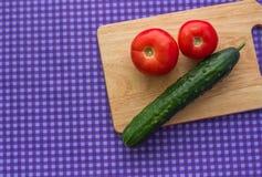 Twee tomaten en een komkommer op een houten Raad op een purpere achtergrond Royalty-vrije Stock Foto