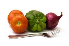 Twee tomaten, groene paprika, rode ui en een vork royalty-vrije stock foto's