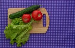 Twee tomaten, salade en een komkommer op een houten Raad op een purpere achtergrond Royalty-vrije Stock Foto's
