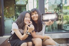 Twee toont het Aziatische gezicht van het tienergeluk het schermvertoning van slim p royalty-vrije stock foto's