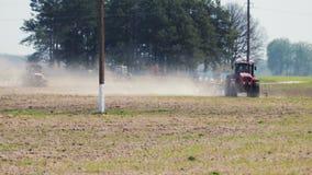 Twee tractoren die van rode kleur de grond in heet droog weer verwerken tegen kolommen van een machtslijn stock video