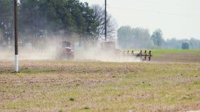 Twee tractoren die van rode kleur de grond in heet droog weer verwerken tegen kolommen van een machtslijn stock videobeelden