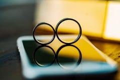 Twee trouwringen in de vorm van nummer acht tribune op een witte telefoon op de lijst De stralen van de zon gaan door over stock foto