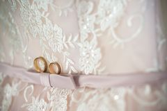 Twee trouwringen die op huwelijkskleding leggen stock fotografie
