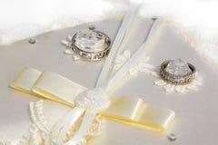Twee trouwringen met witgoud op een kussen stock foto's