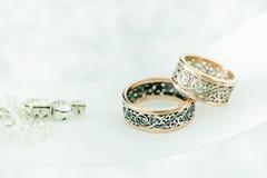 Twee trouwringen met zeldzaam ontwerp op wit breed lint royalty-vrije stock afbeeldingen