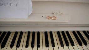 Twee trouwringen op een piano en oude muzieknoten stock videobeelden