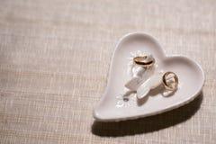 Twee trouwringen op een steun in de vorm van een hart op een lichte achtergrond stock foto's