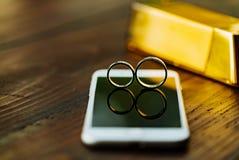 Twee trouwringen zijn op de vertoning van de telefoon Een paar gouden ringen is op de achtergrond van een houten lijst in de ruim stock foto's