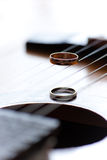 Twee trouwringen zijn op gitaarstrepen Stock Afbeeldingen
