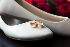 Twee trouwringen zijn op witte balletvlakten en rode rozen stock afbeeldingen