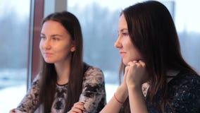 Twee tweelingen in een koffie het luisteren bespreking en wonder stock footage
