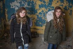 Twee tweelingen op de achtergrond van een gebarsten muur royalty-vrije stock afbeeldingen