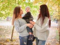 Twee tweelingzusters, tribune in de herfst die een kleine jongen, één parkwatching van wie hen houdt stock afbeeldingen