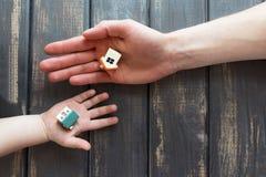 Twee uiterst kleine beeldjes, speelgoed, modellen van huizen ligt op de open hand Stock Foto's