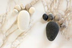 Twee uiterst kleine steenvoet en tien tenen op beige achtergrond, steen in de vorm van menselijke voeten stock afbeeldingen