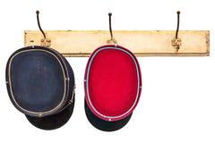 Twee uitstekende leiderhoeden die op hat-rack hangen Stock Foto
