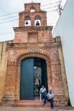 Twee undientified mensen die voor koloniale kerk in Santo Domingo zitten Stock Afbeeldingen