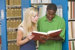 Twee universitaire studenten die in bibliotheek werken Stock Afbeeldingen