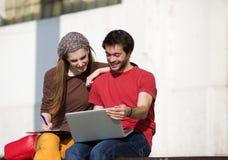 Twee universitaire studenten die met laptop in openlucht bestuderen Royalty-vrije Stock Foto's