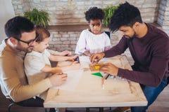 Twee vaders spelen onderwijsspelen met hun kinderen royalty-vrije stock afbeeldingen