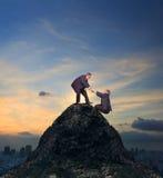 Twee van de Aziatische bedrijfsmens die hand helpen aan het beklimmen tot piek van stock afbeelding