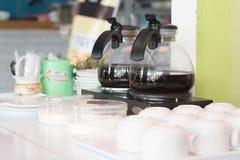 Twee van koffiezetapparaatketel en overvloedskop binnen een gediende cakeopslag royalty-vrije stock foto