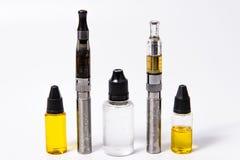 Twee Vape e-Cig en Drie flessen van het vapesap Royalty-vrije Stock Foto's