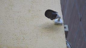 Twee veiligheidscamera's op een baksteen basisschool, die uit meer dan een parkeerterrein kijken stock footage
