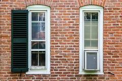 Twee vensters, een airconditioner, en een ontbrekend blind stock afbeeldingen