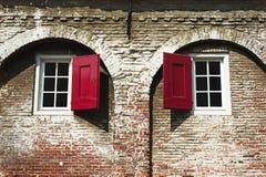 Twee vensters met rode blinden Stock Foto