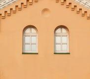 Twee vensters op de gele muur Stock Afbeeldingen