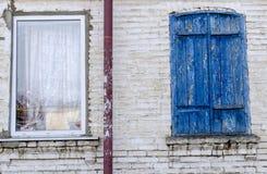 Twee vensters van verschillende stijl op een bakstenen muur Stock Foto