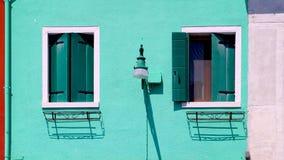 Twee Venstershuis in Burano op groene muur royalty-vrije stock afbeeldingen