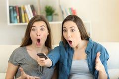 Twee verbaasde vrienden die op TV thuis letten royalty-vrije stock foto