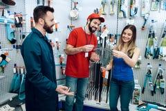 Twee verkopers tonen vrouwelijke cliënt nieuwe hark in de opslag van machtshulpmiddelen stock afbeelding