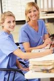 Twee Verpleegsters die bij de Post van Verpleegsters werken stock foto's