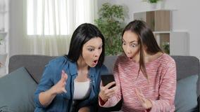 Twee verraste vrienden die telefooninhoud vinden stock videobeelden