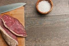 Twee vers gesneden lapjes vlees op een bamboe scherpe raad Stock Afbeeldingen