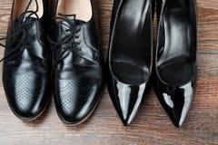 Twee verschillende Paren zwarte klassieke moderne schoenen op de houten vloerachtergrond Royalty-vrije Stock Foto's