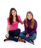 Twee verschillende zusters die op de vloer zitten Stock Foto