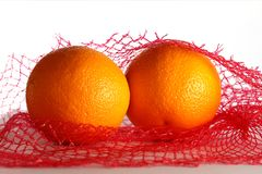 Twee verse sinaasappelen in netwerkzak Stock Foto's