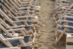 Twee verzettende rijen van opgeschorte lege die ligstoelen in rijen in orde op het strand in het zand worden opgesteld Royalty-vrije Stock Foto's