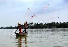 Twee vissers in actie in een kleine boot stock foto
