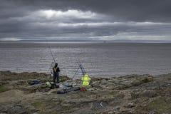 Twee vissers, op de kust op een stormachtige donkere dag stock foto's
