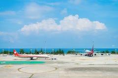 Twee vliegtuigen in de luchthaven met blauwe overzees op achtergrond Stock Fotografie