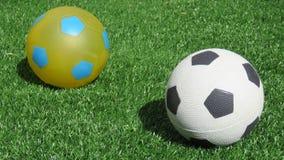 Twee voetballen op gras Stock Afbeeldingen