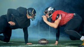 Twee voetballers bevriezen voor elkaar terwijl het spelen van Amerikaanse voetbal stock footage
