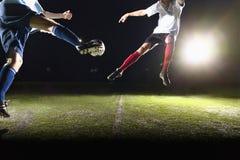 Twee voetballers die een voetbalbal schoppen bij spel Stock Afbeelding