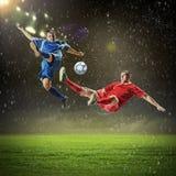 Twee voetbalsters die de bal slaan Stock Foto